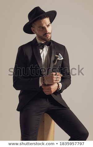 man in tuxedo fixing his sleeve while looking away Stock photo © feedough