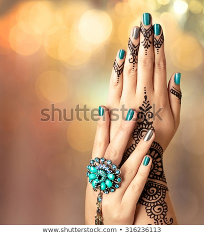 Girl with manicured nails with beautiful ornament in wedding rings holding black fur bag. Stock photo © studiolucky