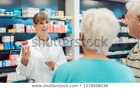 Chemist advising senior couple on a drug in her pharmacy Stock photo © Kzenon