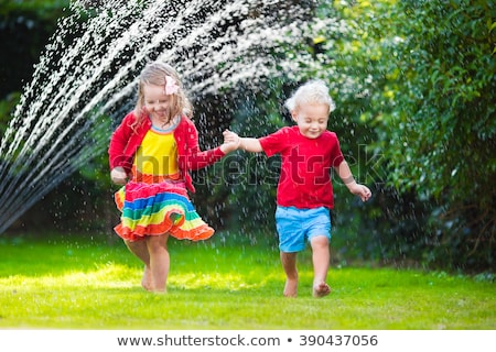 Child playing with garden sprinkler. Kids run and jump. Summer o Stock photo © dashapetrenko