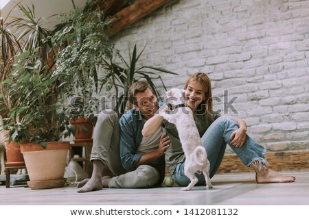 Young couple sitting at rustic living room floor and playing wit Stock photo © boggy