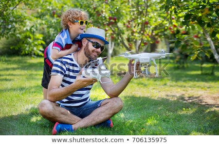 Dad and son playing with drone, man and boy playing with flying drone in sunny garden, happy young b Stock photo © galitskaya