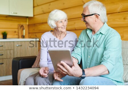 Happy senior spouses in casualwear discussing online data Stock photo © pressmaster