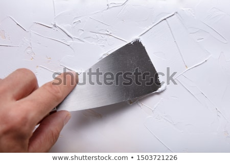 Painter Puttied Wall With Paint Scraper Stock photo © AndreyPopov