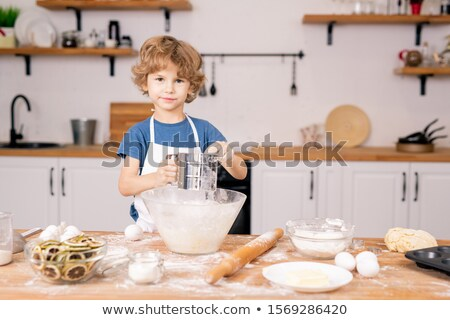 Cute little boy sifting flour over bowl while going to make dough for pastry Stock photo © pressmaster