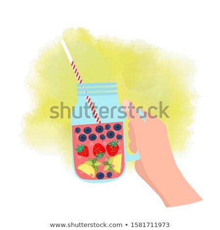 hand holding mason jar with strawberry, blueberry and lemon Stock photo © Margolana