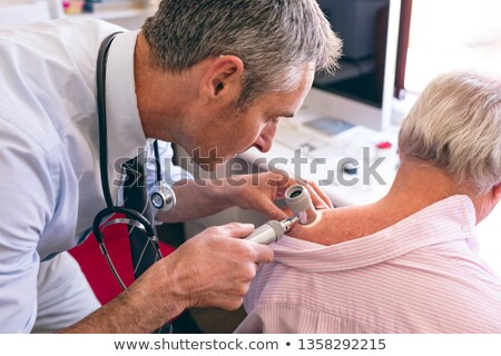 Front view of matured Caucasian male dermatologist examining senior patient with dermatoscopy at cli Stock photo © wavebreak_media
