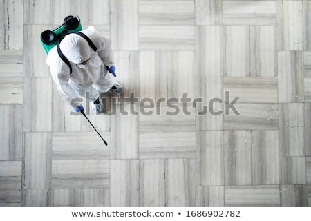 A man in a protective suit disinfects Stock photo © bedlovskaya