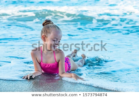 Stock photo: Little girl lies in waves on shore
