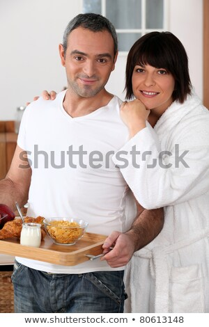 a man bringing breakfast on a platter and his wife wearing a bathrobe stock photo © photography33