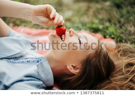 portrait of lying down woman with a strawberry Stock photo © phbcz