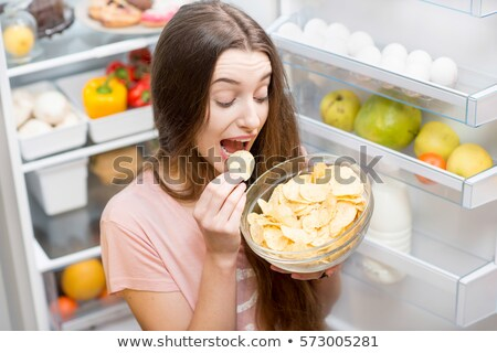 Hungry young woman snacking out of the fridge Stock photo © dash