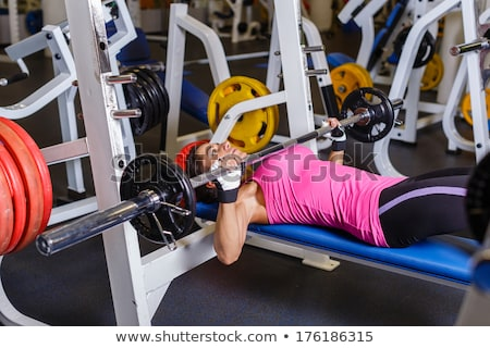 Woman workout with barbell on bench Stock photo © deandrobot