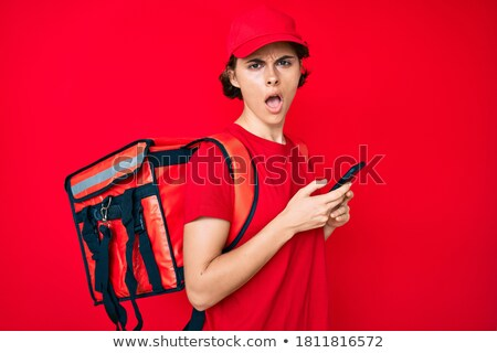 Stockfoto: Surprised Woman With Backpack Holding Smartphone And Looking At Camera