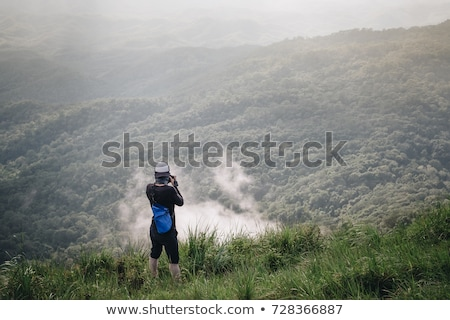 man taking picture on mountain top stock photo © is2