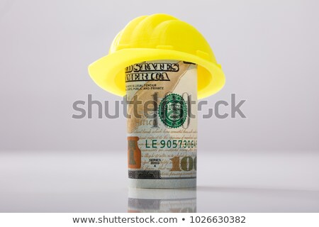 Yellow Hard Hat Over Rolled Up American Banknote Stock photo © AndreyPopov