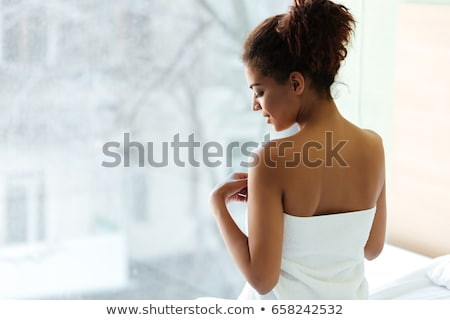 Woman with towel looking out window Stock photo © IS2