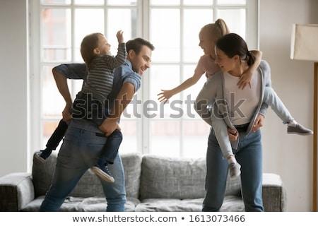 Family of four having fun  carrying the kids piggyback Stock photo © Kzenon