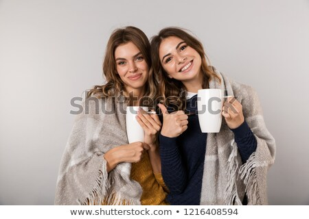 Image of two pretty women covered with blanket holding cups with Stock photo © deandrobot