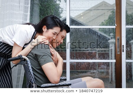 man assisting her handicapped wife to sit on wheelchair stock photo © andreypopov