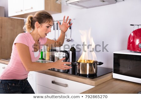 mulher · jovem · olhando · panela · fogo · moderno - foto stock © andreypopov