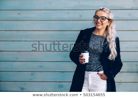 Gorgeous woman walking at street with cup of coffee. Stock photo © studiolucky