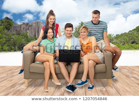 friends with laptop sitting on sofa over beach Stock photo © dolgachov
