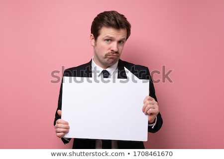 upset businessman holding white empty panel stock photo © lichtmeister