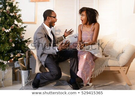Cheerful young woman with giftbox making Christmas present to her granny Stock photo © pressmaster