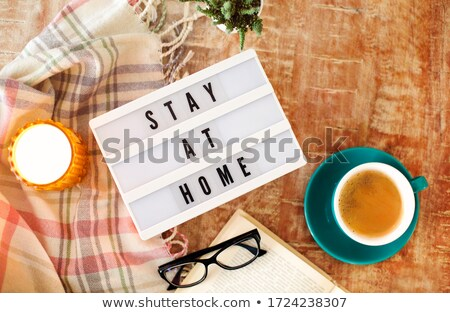 Board with Stay At Home writing, cup of coffee, burning candle a Stock photo © dashapetrenko