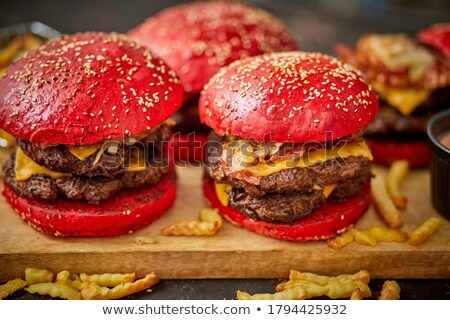 Set of four homemade giant double becon cheese burgers. Served with french fries on wooden board. Stock photo © dash