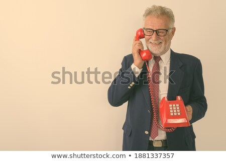 Man in a suit smiling while calling against white background stock photo © wavebreak_media