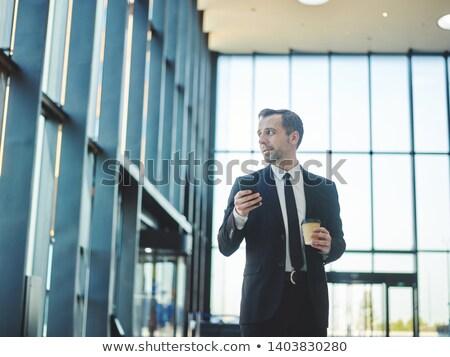 Biznesmen smartphone biurowiec lobby atrakcyjny górę Zdjęcia stock © HASLOO