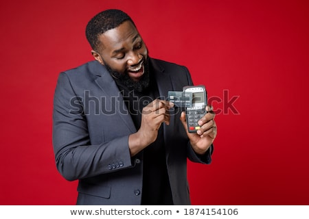 Businessman in black suit holding bank terminal with credit card Stock photo © deandrobot