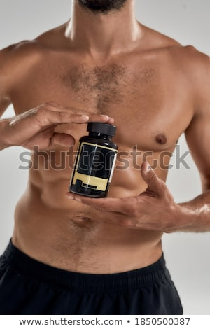 Cropped image of young sportsman holding vitamins and sport pills. Stock photo © deandrobot