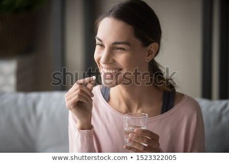 женщину · стекла · воды · таблетки · привлекательный · улыбающаяся · женщина - Сток-фото © LightFieldStudios