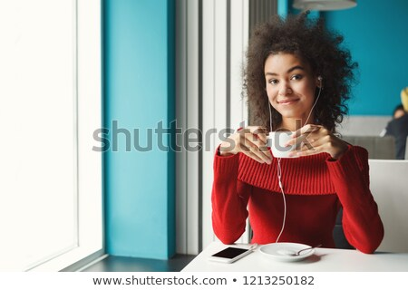 Woman by window to camera with hot drink Stock photo © IS2