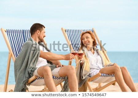Happy couple on lounger with wine Stock photo © IS2