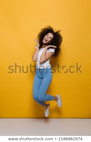 Full length photo of hipster woman 20s with curly hair having fu Stock photo © deandrobot