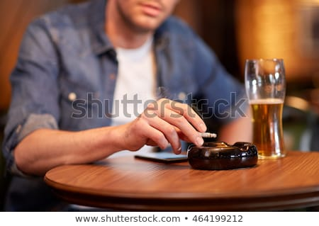 man with cellphone drinking alcohol and smoking Stock photo © dolgachov