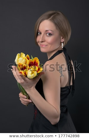 Girl with a tattoo holding on her shoulder an orange flower strelitzia around a blue background with Stock photo © artjazz