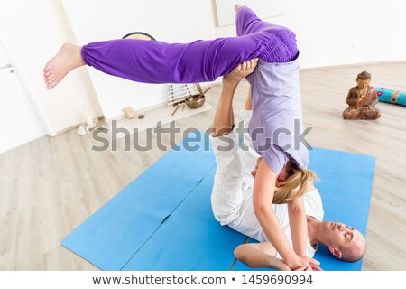 Male instructor balancing female on his two legs Photo stock © Kzenon