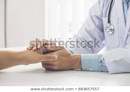 Stock photo: Close up of doctor touching patient hand for encouragement and e
