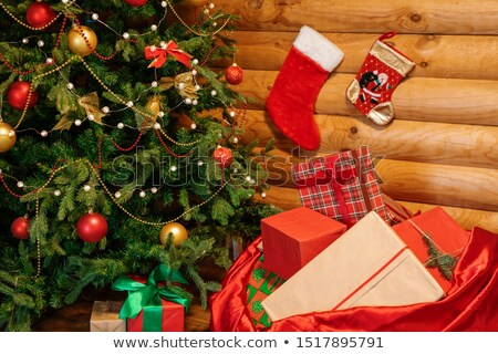 Christmas presents by decorated firtree and wooden wall with two socks for gifts Stock photo © pressmaster