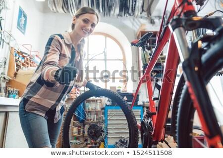 Woman bike mechanic in her workshop changing a tire Stock photo © Kzenon