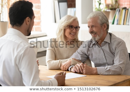 Happy mature spouses listening to real estate or insurance agent explanations Stock photo © pressmaster