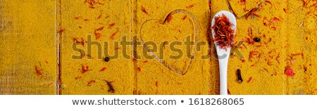Banner with Heart of spices and seasonings. White spoon with saffron on curry background. Stock photo © Illia