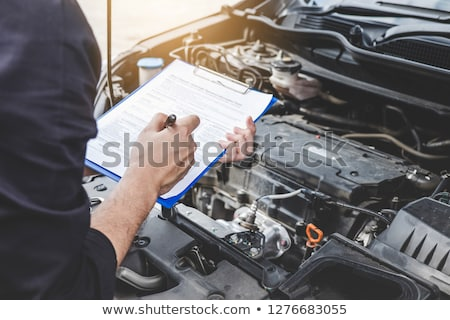auto mechanic with oil and clipboard at car shop Stock photo © dolgachov
