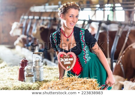 Bavaria woman driving pushcart in cow barn Stock photo © Kzenon