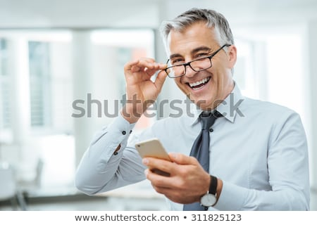 Handsome businessman in glasses adjusting his tie Stock photo © deandrobot